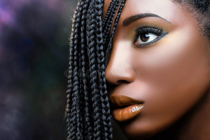 African beauty female face with braids . Macro close up african beauty face shot of young woman with braids. Professional make up fantasy portrait of attractive stock image