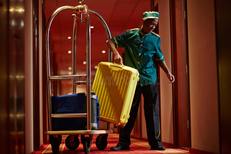 African Bellboy Delivering Luggage to Hotel Rooms. Portrait of African bellboy with luggage cart in hotel hallway, bringing bags to guest rooms royalty free stock image