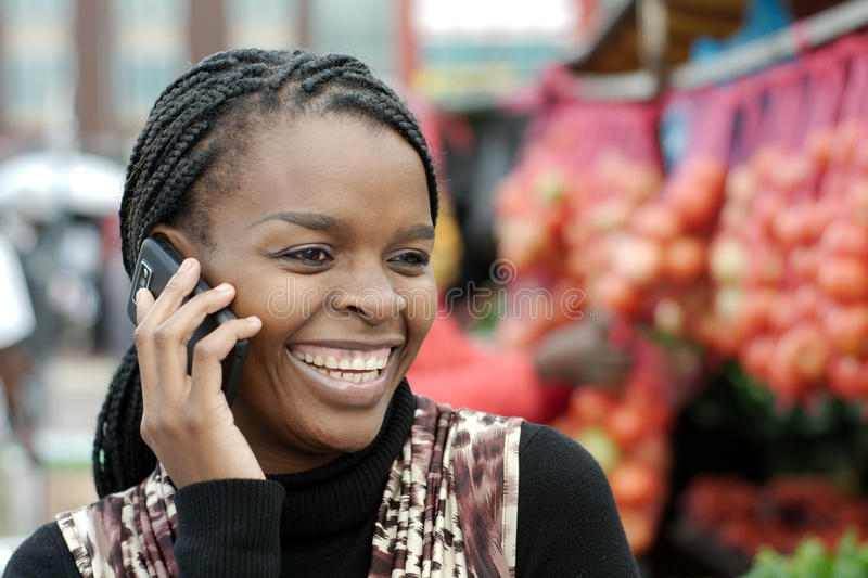 African or black American woman calling on landline telephone. African or black American woman calling on landline payphone telephone in Alexandra township stock image