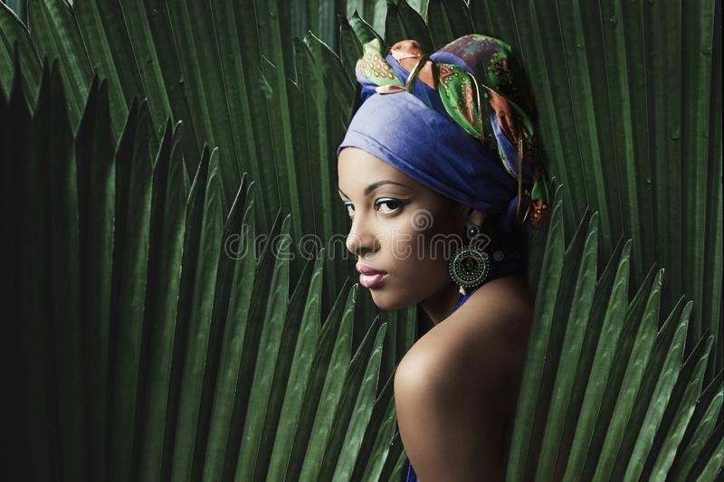 African black young woman beauty portrait with colorful turban headscarf  with palm tree leaves stock photography