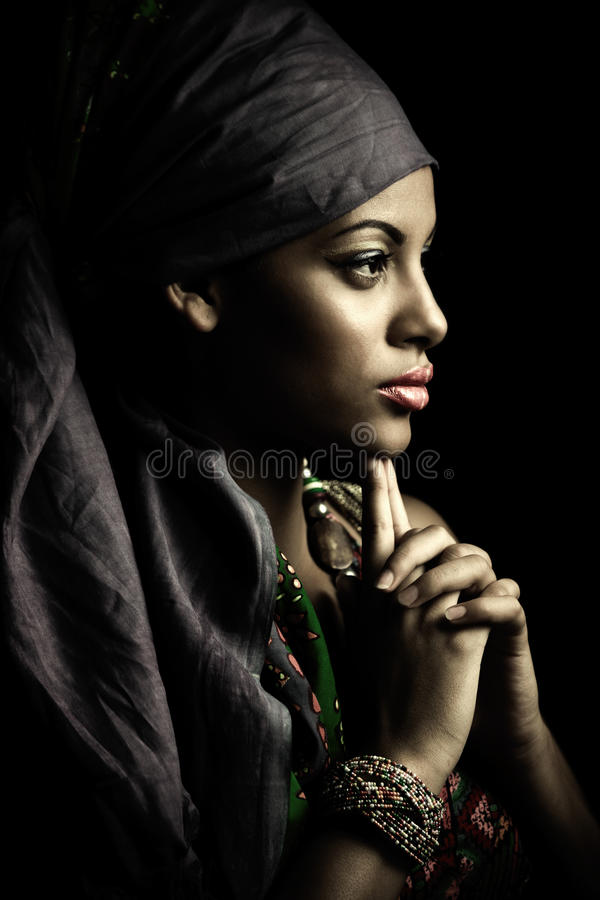 African black young woman beauty portrait with turban studio shot. African black young woman beauty portrait with turban headscarf profile muted colors studio stock photography