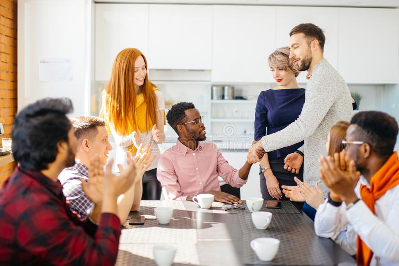 African boss is congratulating his talented worker in front of employees. In break royalty free stock image