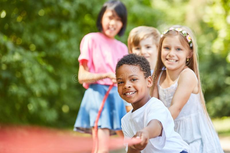 African boy and friends in tug of war royalty free stock image