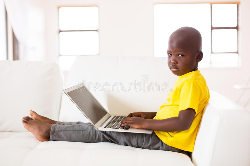 African boy laptop computer. Little african boy with a laptop computer sitting on couch royalty free stock photos