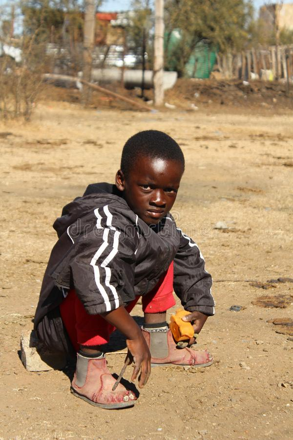 African boy sitting on a stone in a village royalty free stock photos