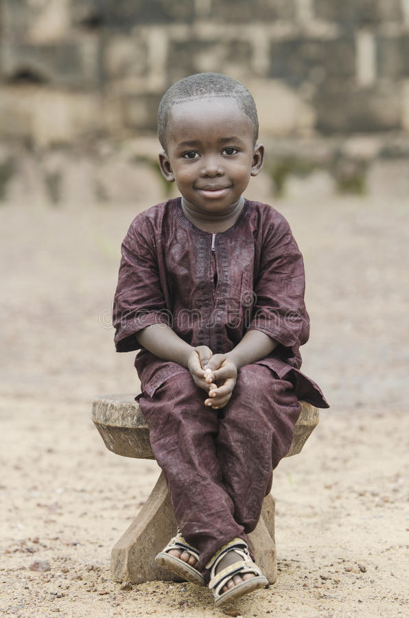 African boy sitting on wooden bench and looking at camera with blurred background stock image