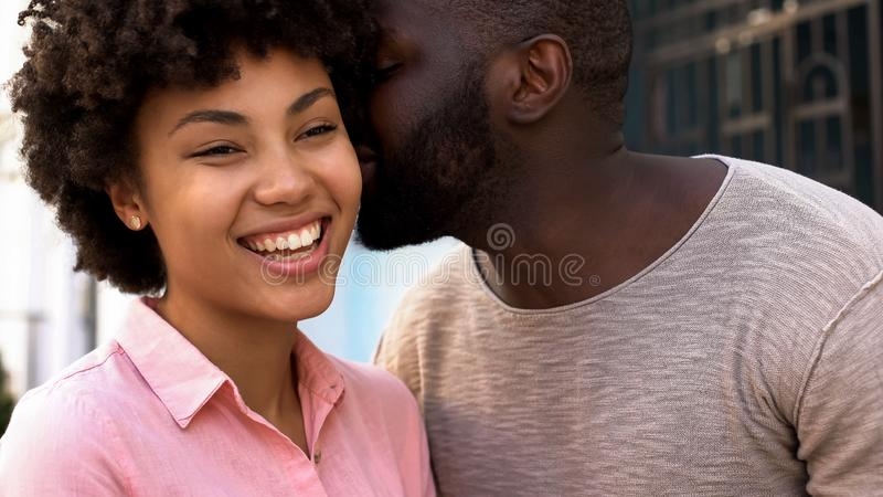 African boyfriend whispering words of love to girlfriend, happy smiling couple royalty free stock image