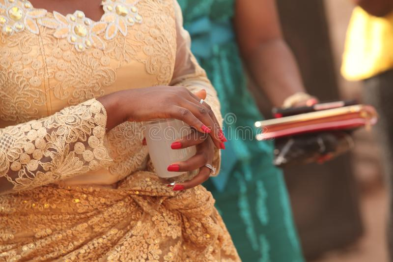 African Traditional Wedding 136. African bride carries palm wine in a cup in public, accompanied by her maiden friends `in search ` of her groom. Whoever she royalty free stock images