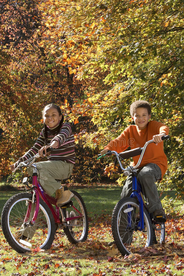 African brother and sister riding bicycles in autumn stock image
