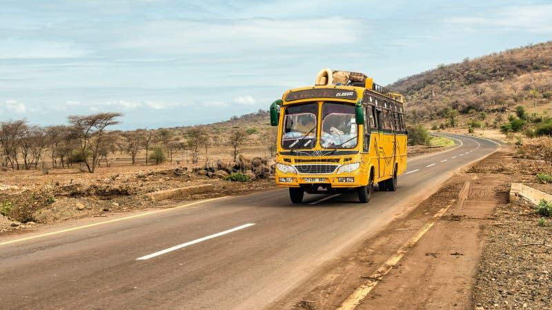 African bus travelling from Arusha to Namanga, Tanzania. MONDULI, TANZANIA - OCTOBER 21, 2014 : Typical and overcrowded african bus driving from Arusha to stock image