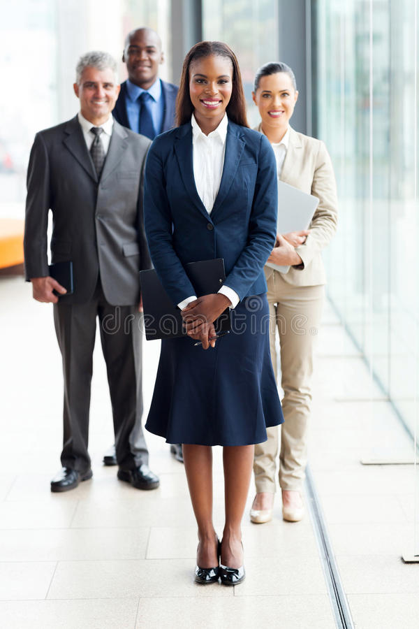 African business leader. Beautiful african female business leader with team standing on background stock image