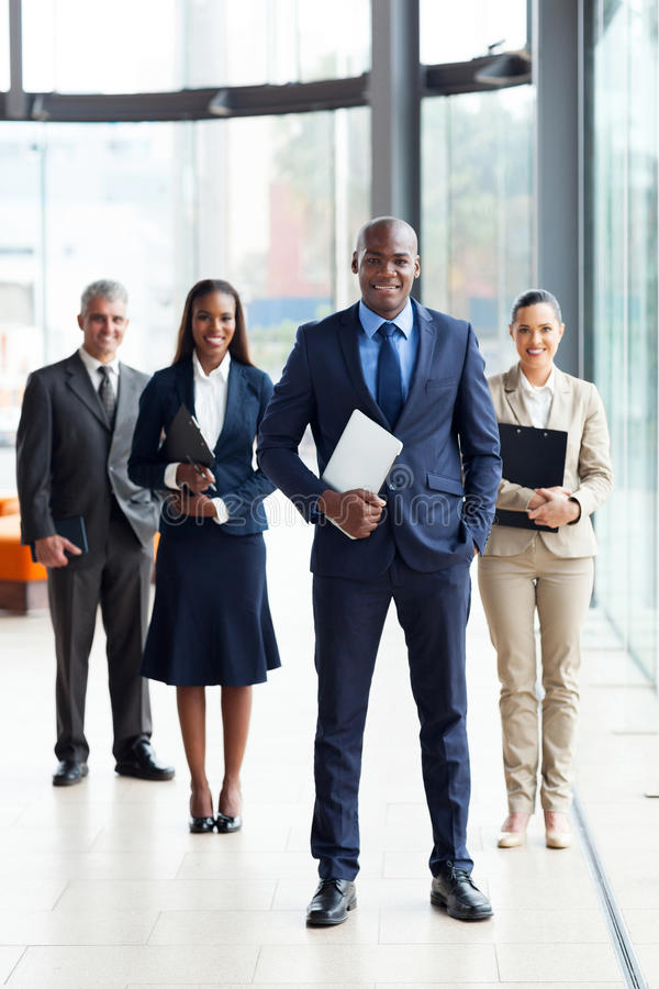 African business leader. Confident male african business leader and team in office royalty free stock photography