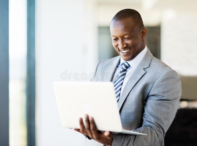 African business man laptop. Smart african business man using laptop in office stock image