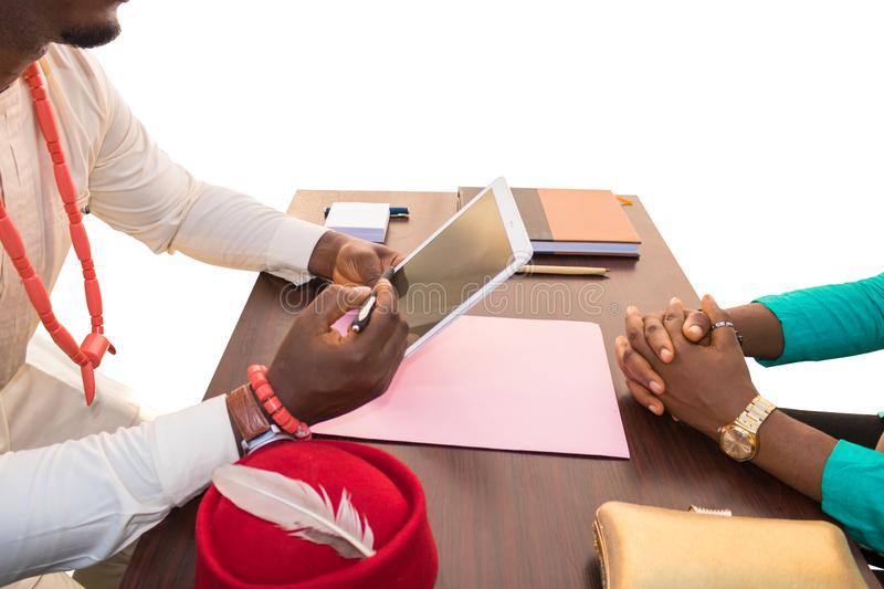 Discuss New Business in Africa. African business men explains to a women with a stylus and tablet from a tablet over an office table isolated in a white stock images