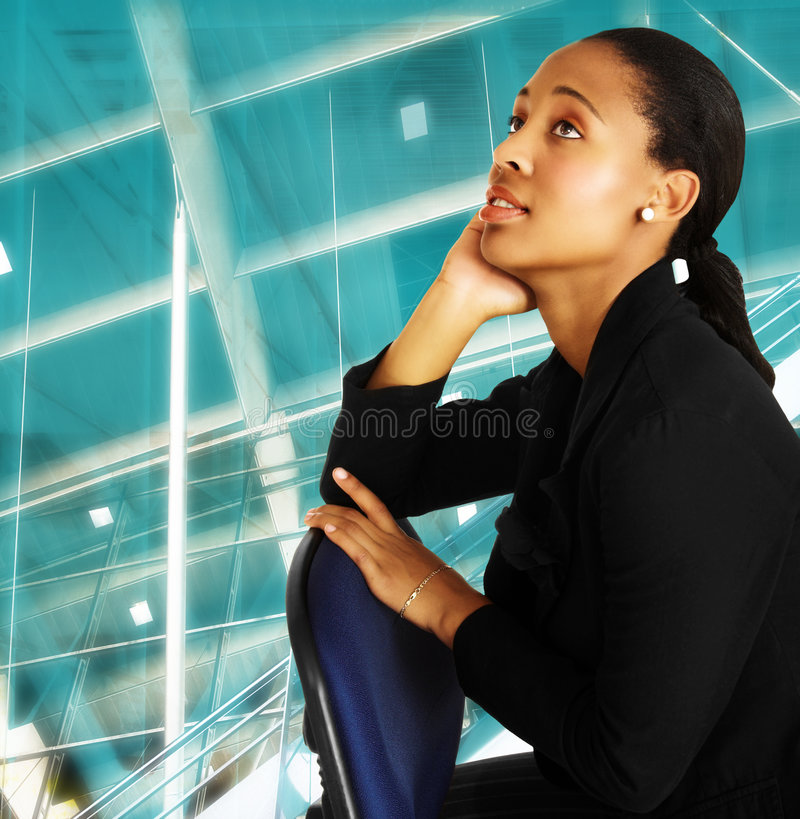 African business woman. Beautiful African business woman in black suit sitting on chair on abstract office background stock images