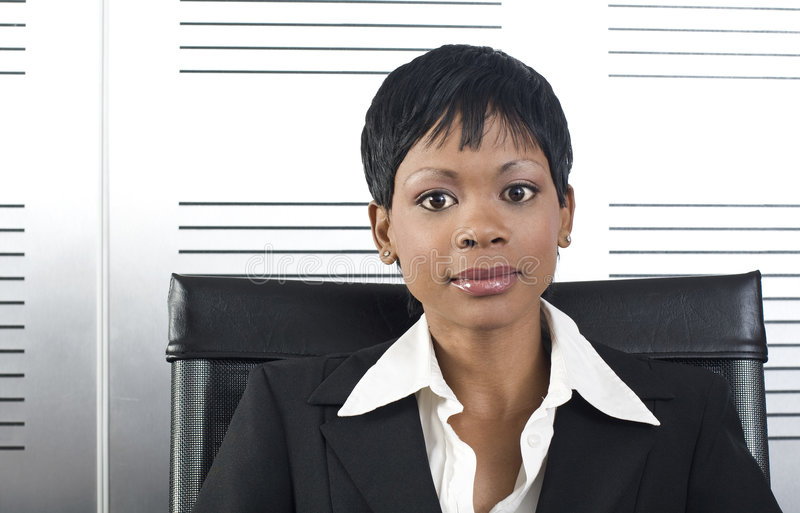African Business Woman. Young attractive african business woman in a modern office setting stock photos