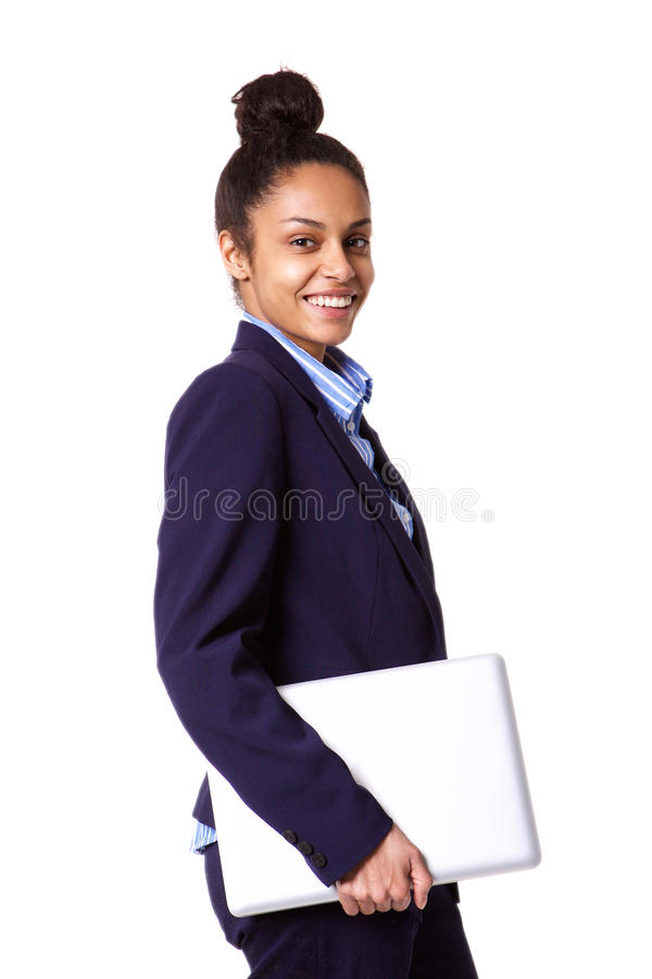 African business woman smiling and holding laptop. Portrait of african business woman smiling and holding laptop in hand against white background stock photo