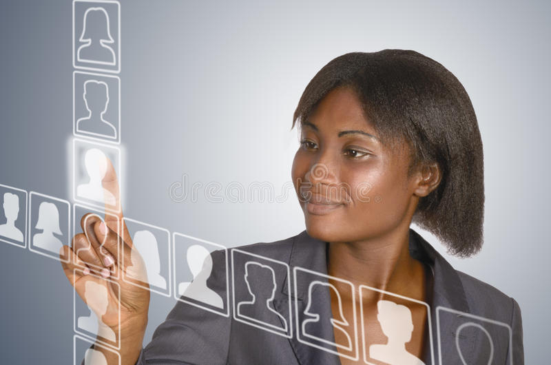 African business woman, social network. African business woman touching virtual touchscreen, studio shot royalty free stock photography