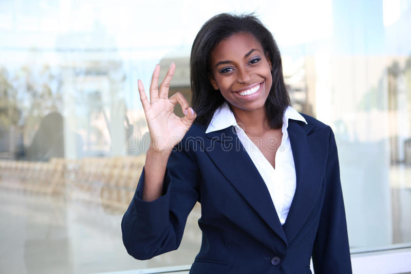 African Business Woman Success. A pretty african american business woman signaling success at office stock photos