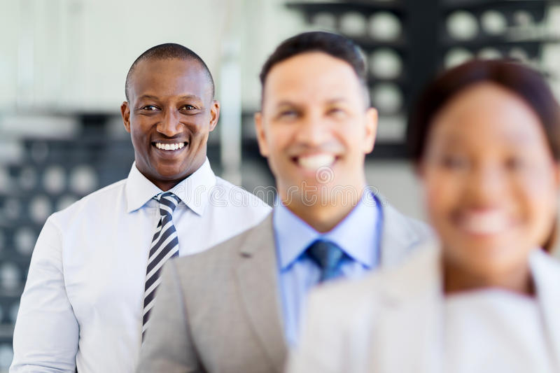 African businessman business team. Happy african businessman standing in a row with business team stock photos