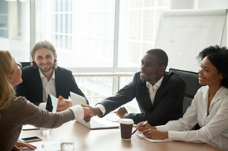 African businessman and caucasian businesswoman shaking hands at royalty free stock photography