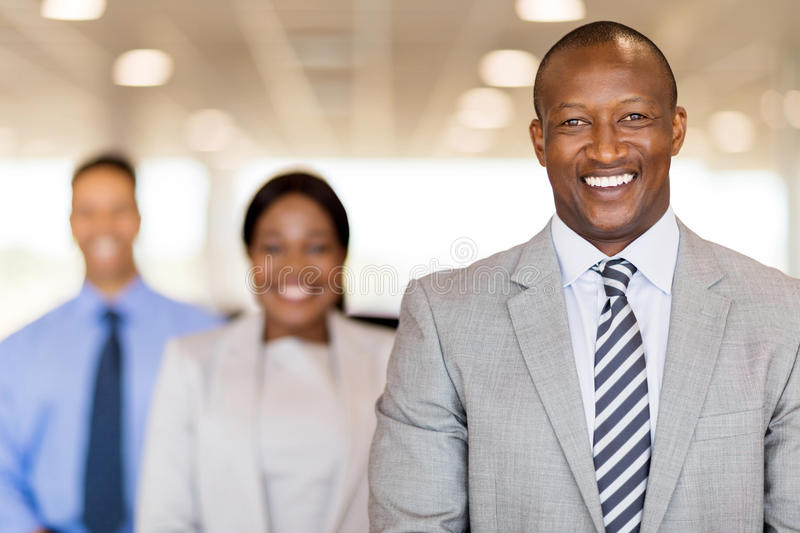 African businessman colleagues. Handsome african businessman standing in front of colleagues royalty free stock images