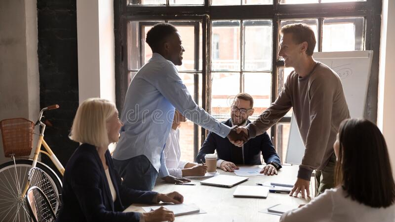 African businessman company executive manager handshaking with european client stock photos