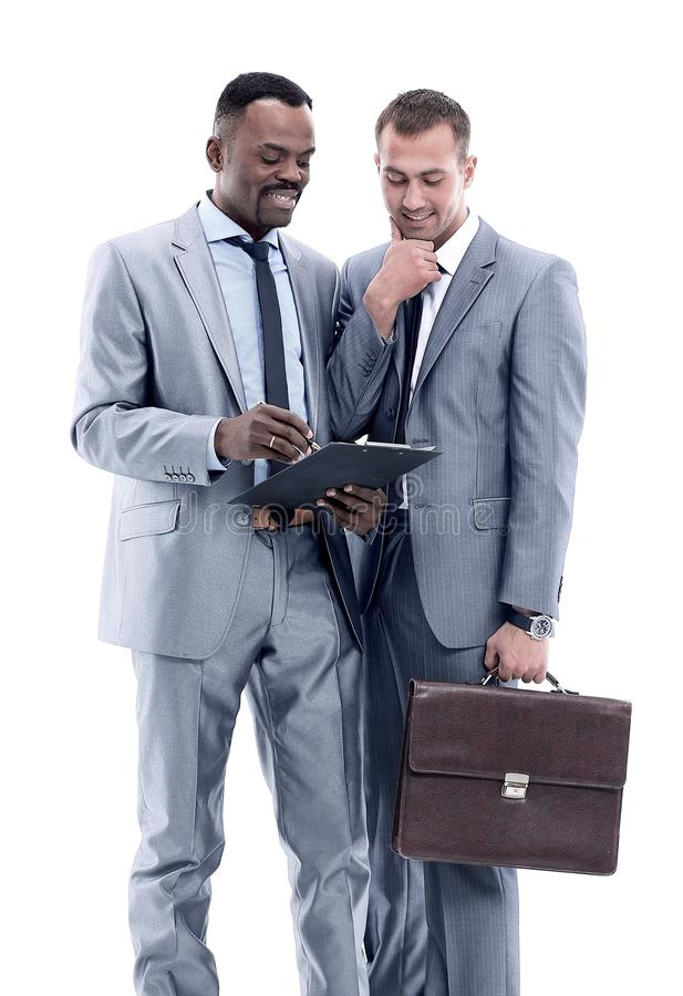 African businessman discussing with colleague. Isolated studio shot of two businessmen brainstorming and taking notes in a notebook royalty free stock photo