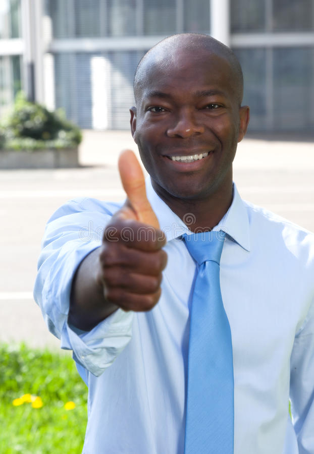 African businessman in front of his office showing thumb. Happy laughing african businessman with tie in front of his office showing thumb royalty free stock images