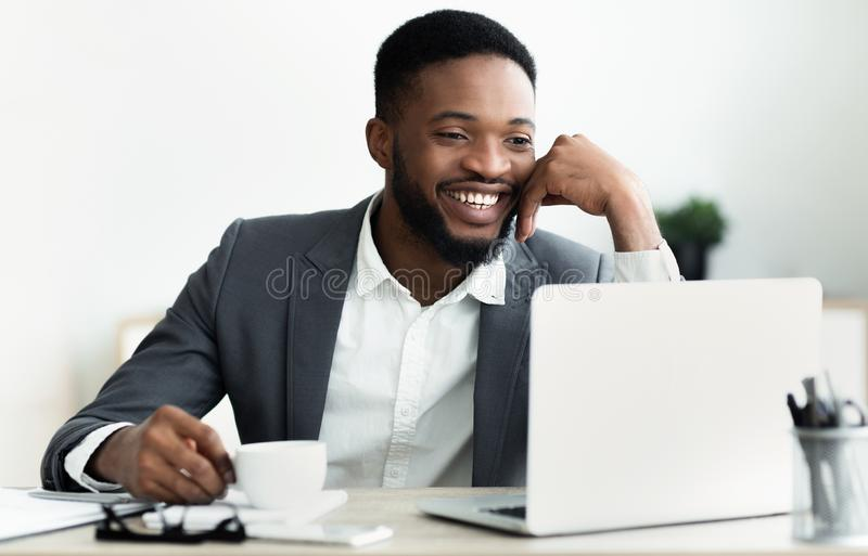 African businessman making video call to family during coffee break. Happy African businessman making video call to family using laptop during coffee break in stock image