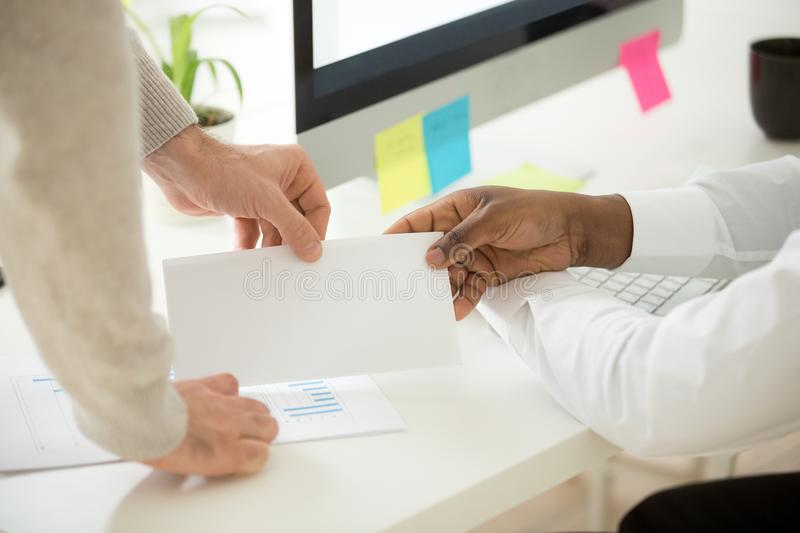 African businessman receiving envelope with bribe or money bonus. African businessman receiving bribe or money bonus from partner client boss at work, bribery in stock photography