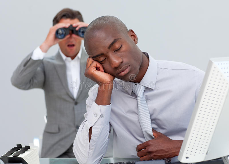 African businessman sleeping. While is manager watching him with binoculars stock images