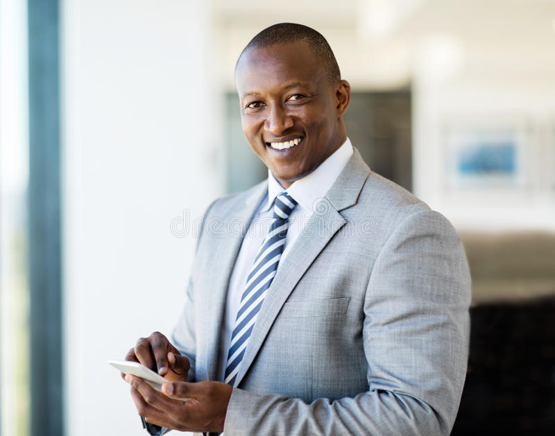 African businessman smart phone. Portrait of smiling african businessman using smart phone in office stock photos