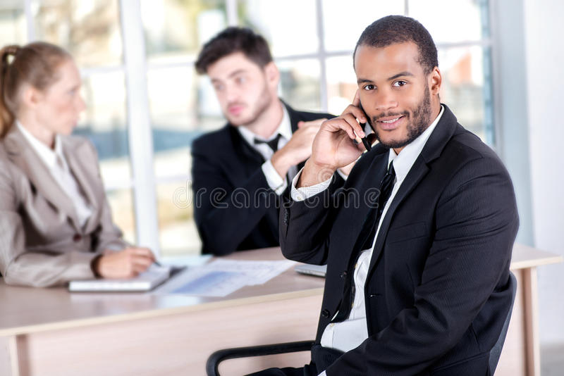 African businessman talking on his mobile phone. Three successful business people sitting in the office and do business while bus stock photos