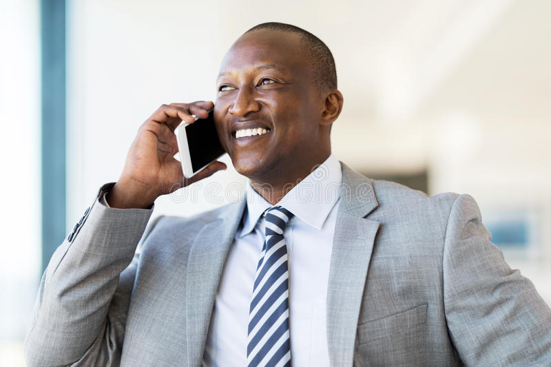 African businessman talking phone. Handsome african businessman talking on cell phone royalty free stock photo