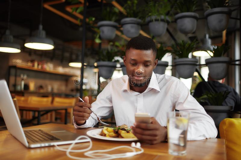 African businessman working and having dinne at restaurant. royalty free stock photos