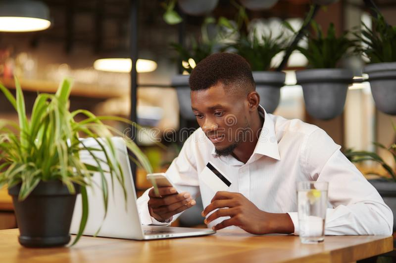 African businessman working with laptop and paying with credit card. stock image