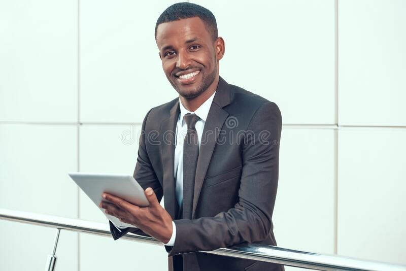 African Businessman Working on Tablet and Smiling. royalty free stock images