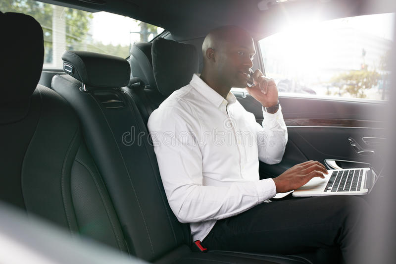 African businessman working during travelling to office in a car stock photo