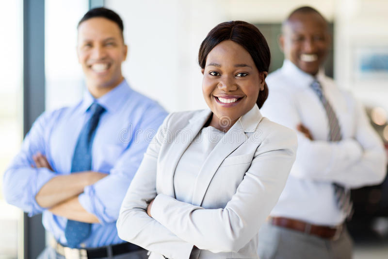 African businesswoman colleagues. Pretty african businesswoman and colleagues with arms folded stock image