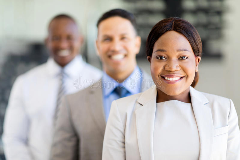 African businesswoman colleagues. Smiling african businesswoman with colleagues standing in a row royalty free stock photography