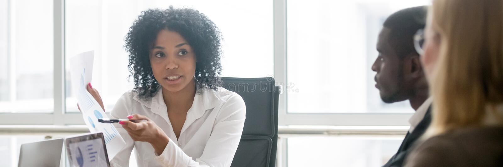 African businesswoman showing document with financial indicators to diverse colleagues stock photos