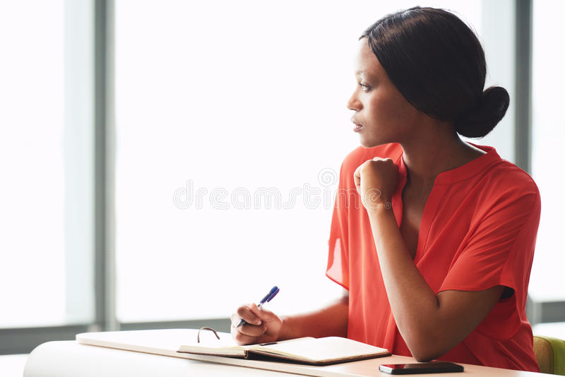 African businesswoman taking a break from her intensive writing session. Young black businesswoman taking a little break from her work while looking out the royalty free stock photography