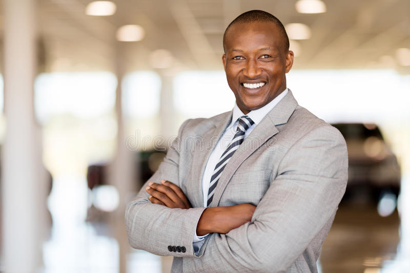African car sales consultant. With arms folded in showroom royalty free stock images
