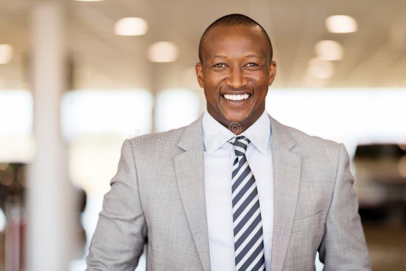 African car salesman showroom. Happy african car salesman in showroom royalty free stock photography