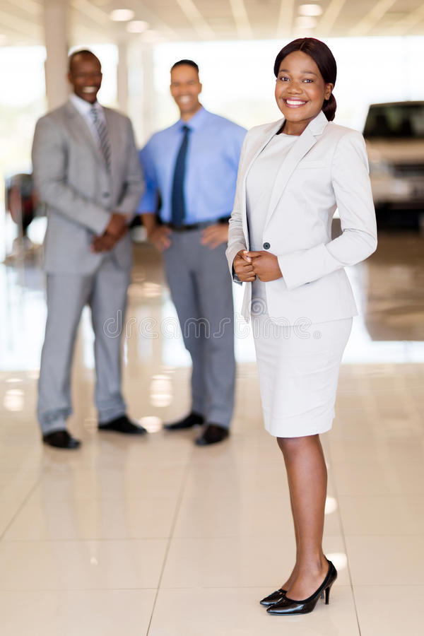 African car saleswoman team. Portrait of african car saleswoman with team on background royalty free stock photos