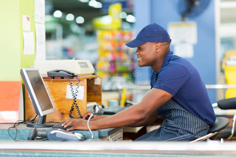 African cashier till point. Happy african male cashier working at till point in supermarket royalty free stock photos