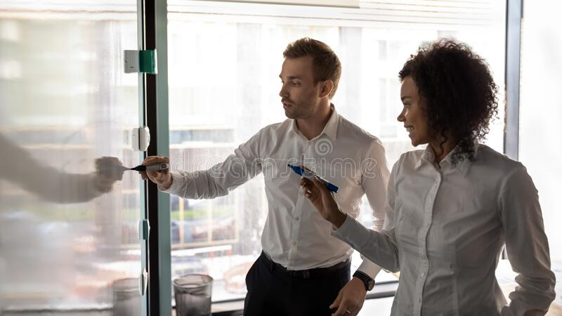 African and caucasian entrepreneurs writing on white board presentation royalty free stock photography