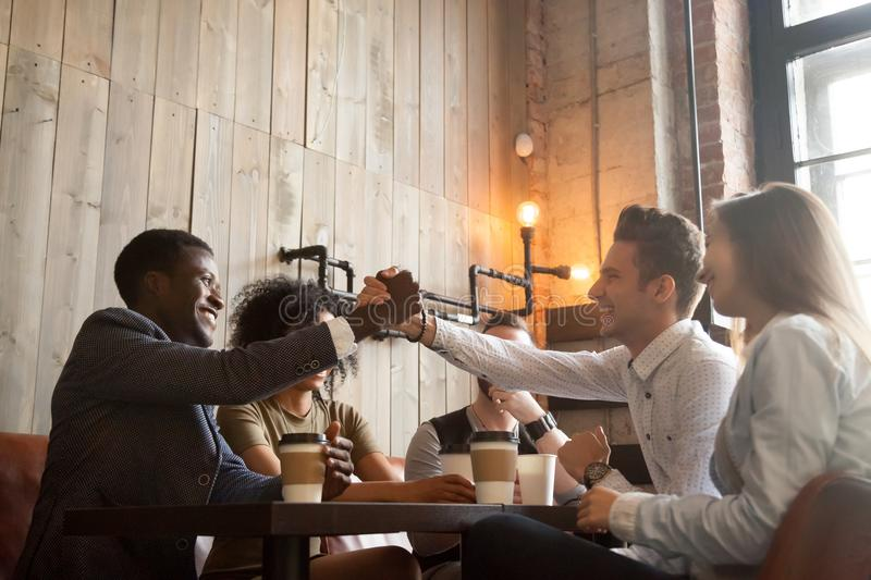 African and caucasian men handshaking at coffeehouse meeting wit stock images