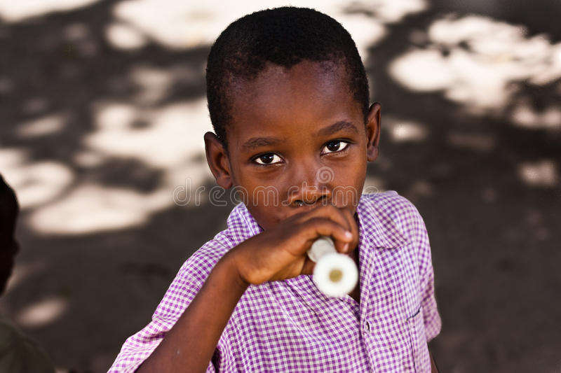 african Child playing his flute stock image